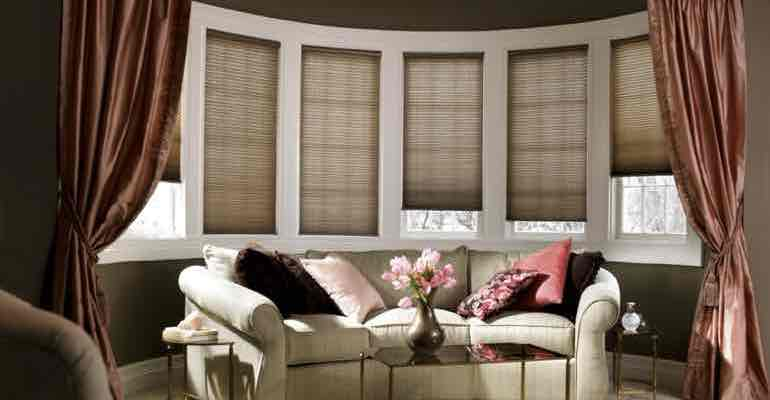 Adjustable cellular shades in living room bow window.