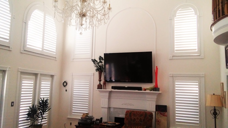 Kingsport great room with wall-mounted television and arched windows.