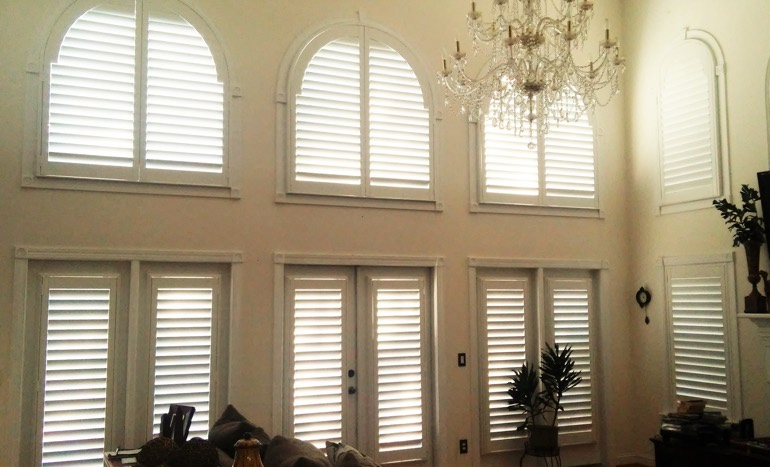 Great room in open concept Kingsport home with plantation shutters on arch windows.