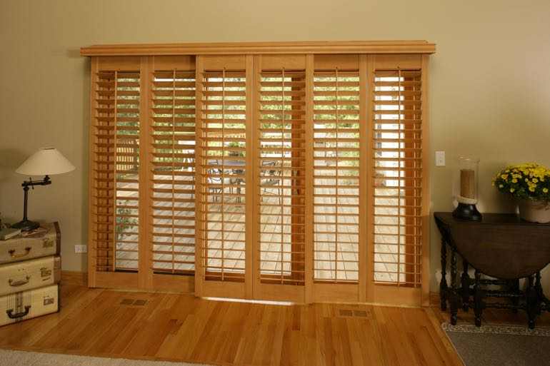 plantation shutters on sliding door connecting to outdoor porch.