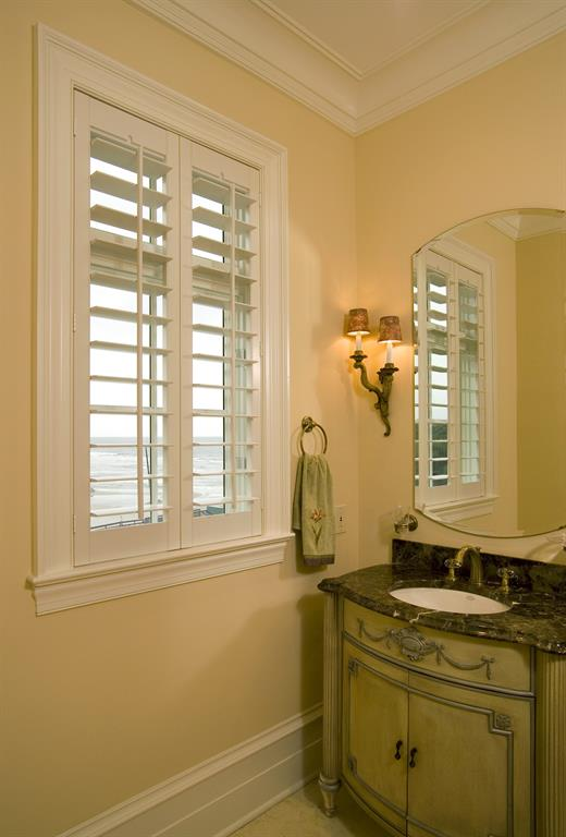 Plantation shutters in a light bathroom outlooking the ocean