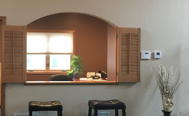Shutters framing out a cutout between the kitchen and living room