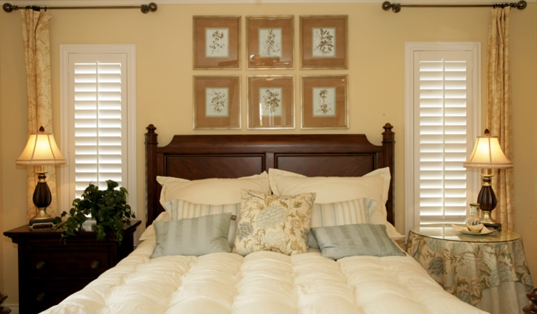 Beige bedroom with white plantation shutters covering windows in Kingsport