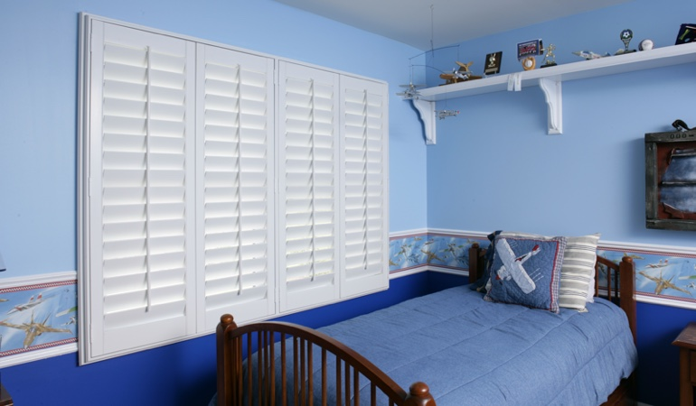 Large plantation shutters covering window in blue kids bedroom in Kingsport